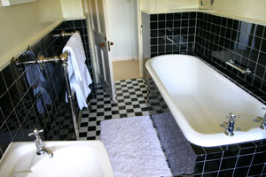 The bathroom with 1920s tiling and the original Victorian Bath