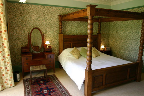 Tinto Bedroom with four poster bed, Edwardian furniture and William Morris wallpaper